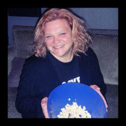 Amanda of Reno band Basement Tapes holding popcorn and smiling.