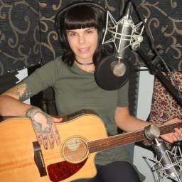 Reno songwriter Jenni Ojibwe posing with her guitar in the studio recording the Worst Little Podcast.