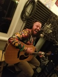 Reno singer-songwriter Liam Kyle Cahill playing guitar and singing while recording for the Worst Little Podcast at Dogwater Studios.