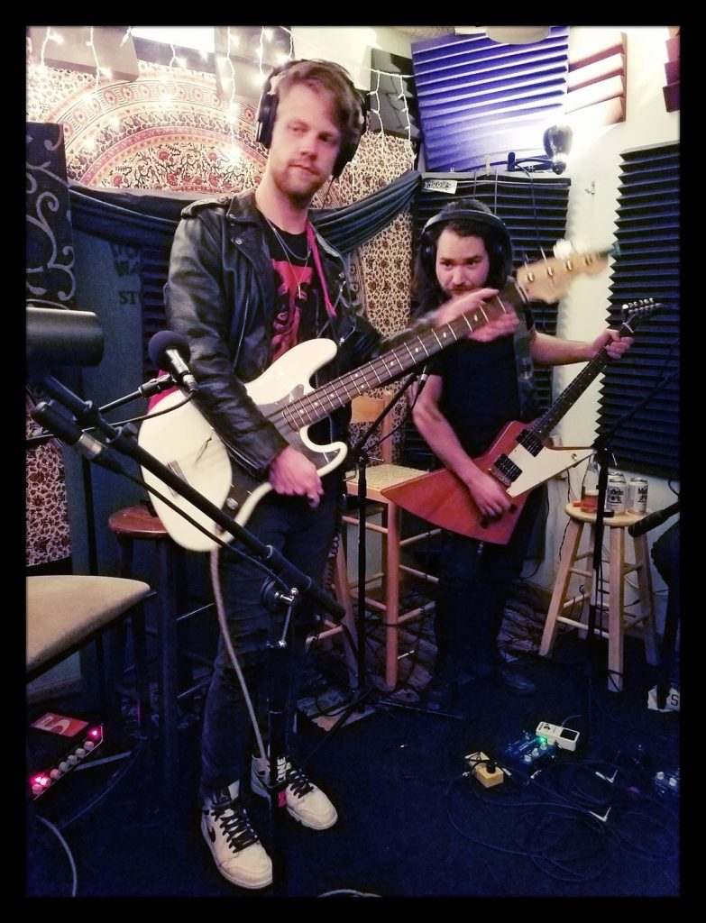 Honkey and Jimmy from Reno Nevada band Skew Ring playing guitars at Dogwater Studios while recording the Worst Little Podcast .
