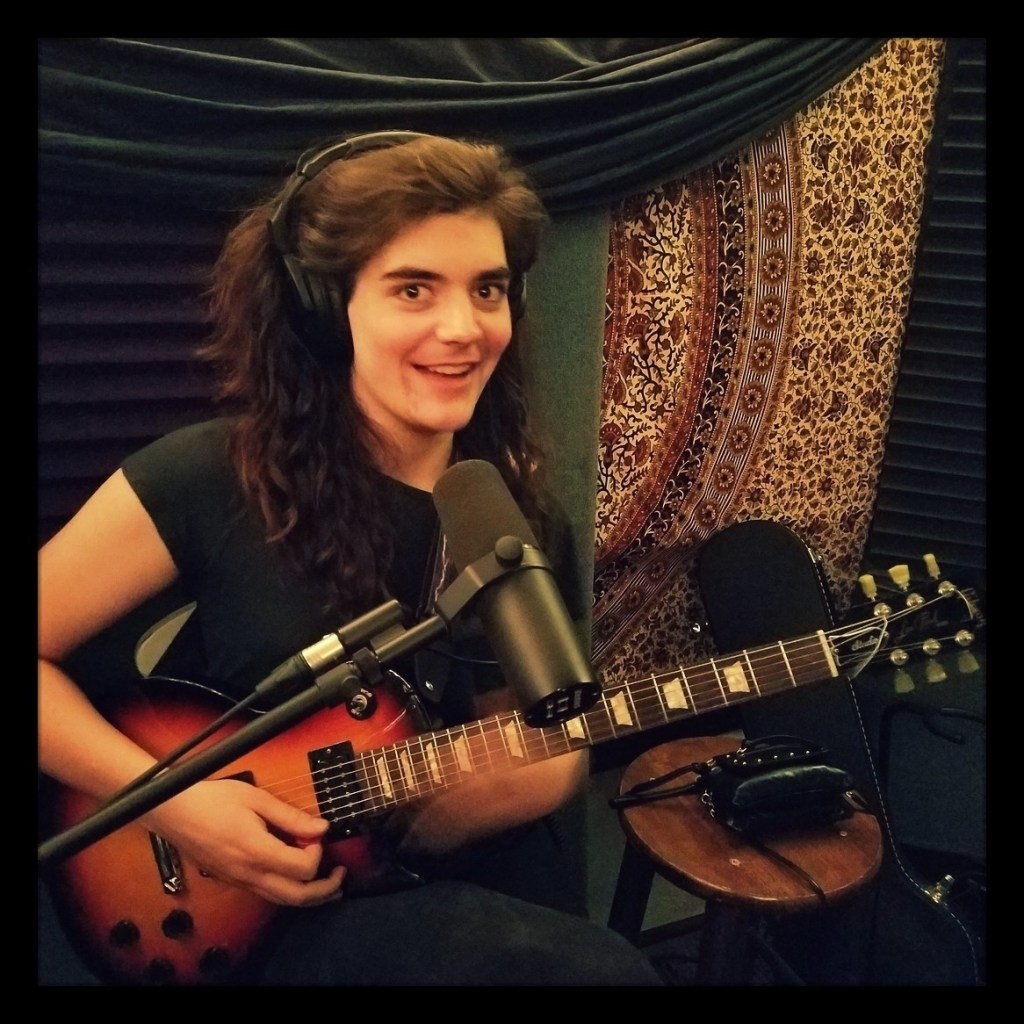 Elleanor smiling for the camera while holding her guitar in the recording studio for the Worst Little Podcast.