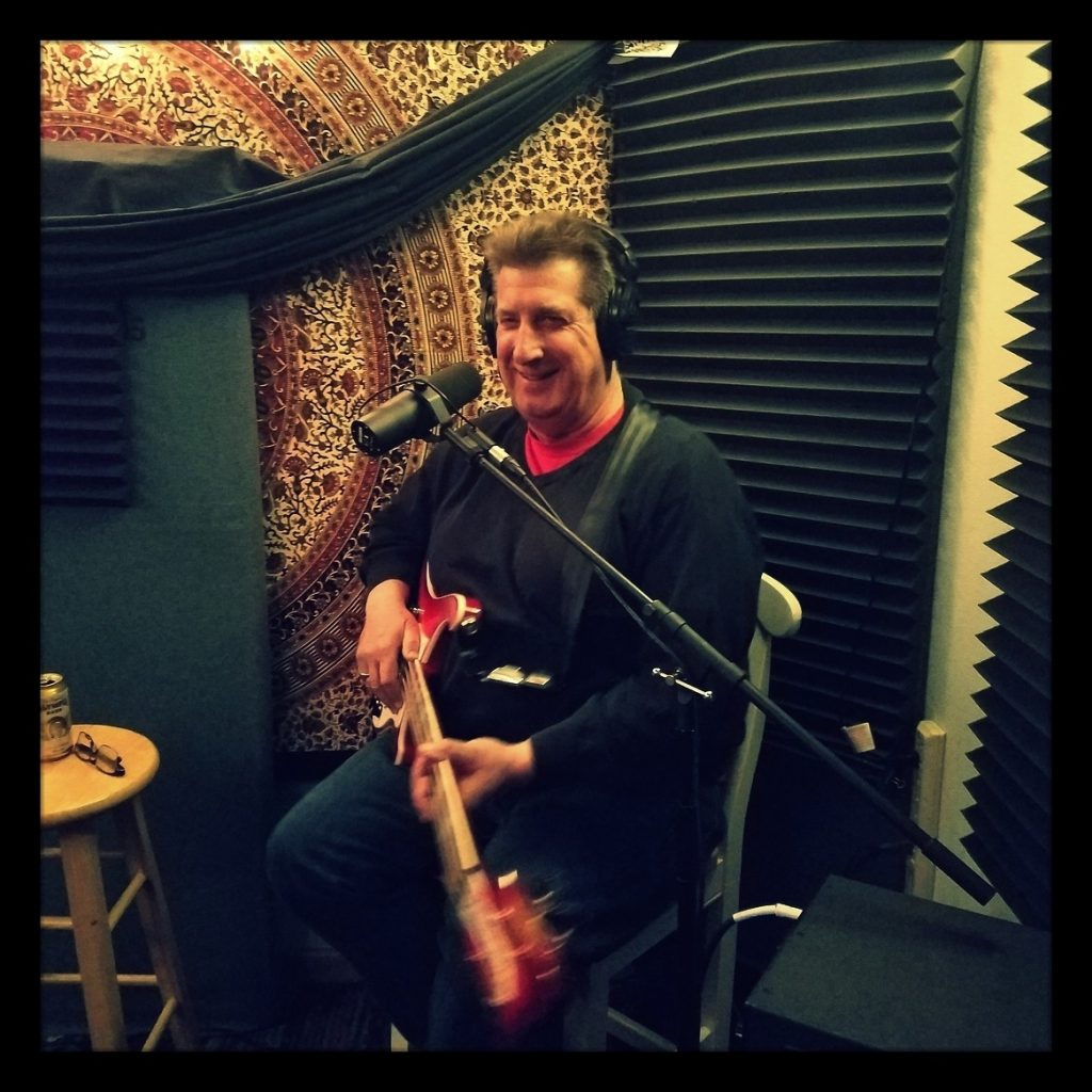 Big John from Reno band Cowboy Indian holding his bass and smiling.