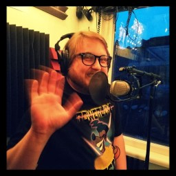 Intern Shrek waves to the camera while sitting behind the mic at Dogwater Studios.