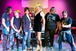 lineup of the cast in their rock and roll costumes and in character poses.