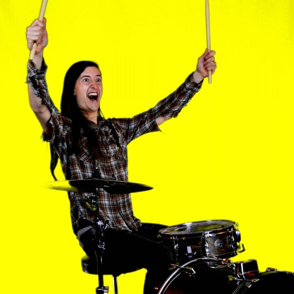 Felipendejo smiling maniacally holding drumsticks aloft against a yellow background