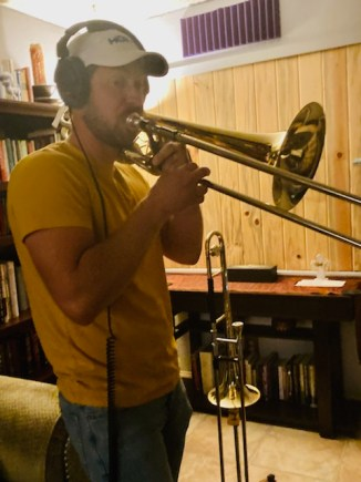 Eric on the bass trombone in a yellow shirt