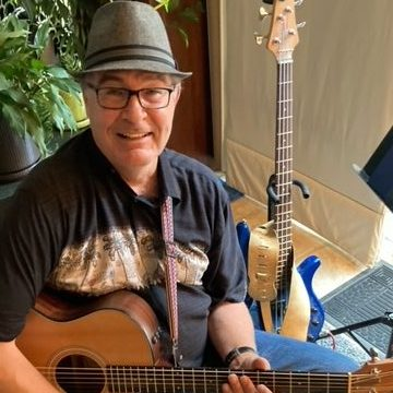 Multi-instrumentalist, Doyle Wayne Stewart holding an acoustic guitar with his blue electric bass behind him.