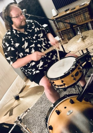 Tyler on the drums in a Hawaiian print shirt