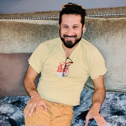 A bearded Baldo Bobadilla smiling broadly from the downstairs couch at Dogwater Studios.