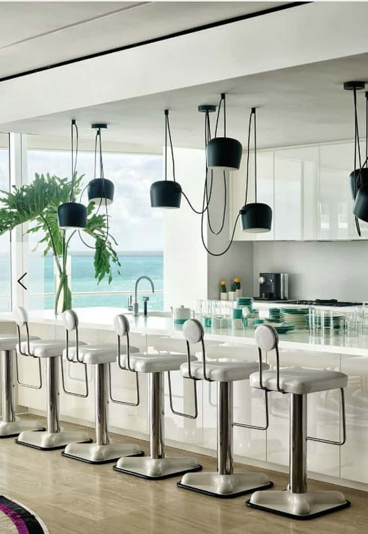 white kitchen with contemporary stools and black pendants