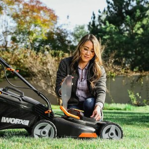 woman kneeling grass and placing battery into Worx cordless lawn mower