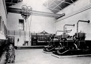 SWEHS 7.1.066.jpg - Date 1902 - Carn Brea engine room in 1902 when supply was commenced. The two Belliss & Morcom 90kW sets conceal most of the 45kW set. The balancers and boosters are on the left and the Hayle telephone is between the door and low voltage board. Cornwall, Carn Brea Station initially operated by Urban Electric Supply Company and then taken over by Cornwall Electric Power Company (Edmundsons) in 1906. Ceased generation 1911 when rotary converters installed for the trams..