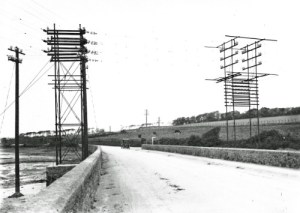SWEHS 7.1.112.jpg - Date 1911 - The angle pole of the 10kV dual circuit from Hayle to Nancledra. On left is connection to St Erth Dredge. Cornwall, Hayle Causeway The telephone wires below the cradle guard include cable land lines between London and Portcurno and London and Sennen..