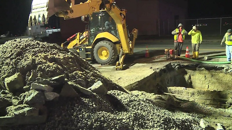 An excavating power shovel extends down into a hole on Airport Road as Warwick city crews work to fix a water main break, November 4, 2019. (WPRI-TV/James Pilkington)
