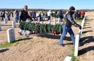 Bryan Correira | Herald Two volunteers carry a pole filled with wreaths at the Central Texas State Veterans Cemetery on Sunday, Jan. 5, 2014. Some 5,000 wreaths that adorned the graves of veterans were removed.