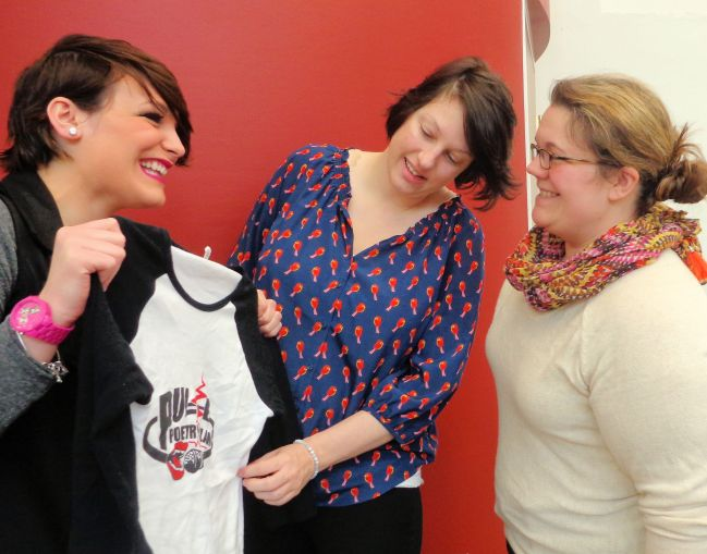 "Autumn Echo Swanson, founder of Pulse Poetry Slam and emcee for a poetry slam at 6 p.m. Thursday, March 26 at Prendergast Library, shows a promotional T-shirt to Allison Brake, library visitor, and Liz Gruber, librarian. The library's poetry slam will kick off this year's Big Read featuring ""The Great Gatsby"" by F. Scott Fitzgerald."