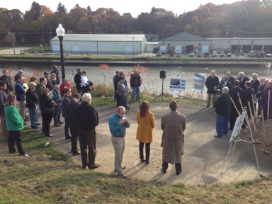 Several community members gathered for Tuesday's groundbreaking ceremony at the Greater Jamestown Riverwalk where one of the two pedestrian bridges will be built.