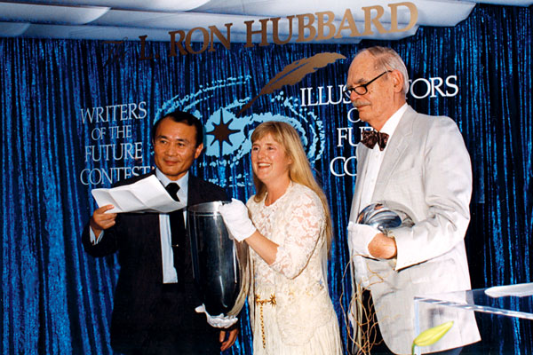 Dr. Yoji Kondo and Frederik Pohl help guest speaker Nancy Cartwright prepare the annual time capsule.