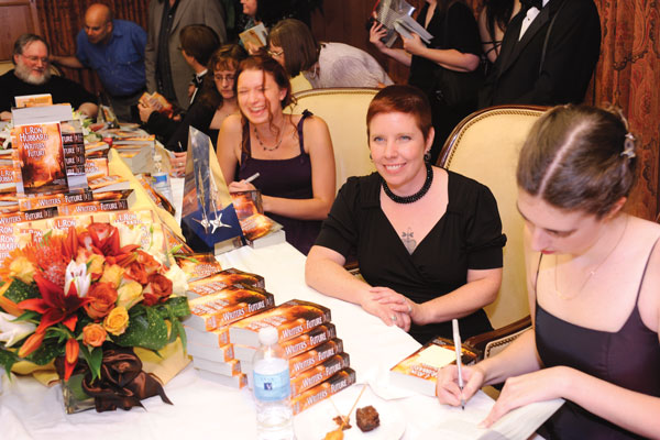 J. D. EveryHope, Laura Bradley Rede and Sarah L. Edwards autograph the anthology.
