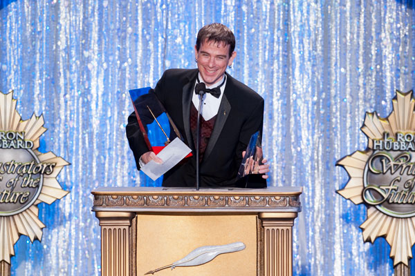 Seth J. Rowanwood, Golden Brush award-winner, on stage accepting his award.