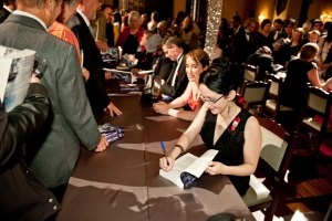 Writer Winner Megan O'Keefe autographs her story for guests.