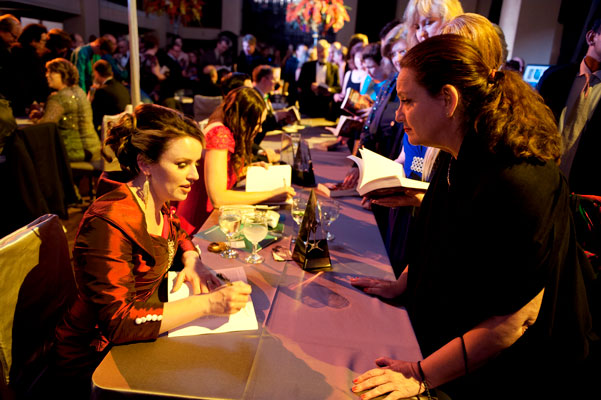 Amy Hughes autographing copies of Writers of the Future Volume 31 for a fan.