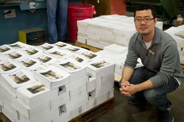Choong Yoon at Bang Printing next to a pallet of unbound books with his illustration.