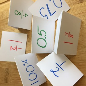 Tent cards with fractions, decimals and percents in red, green and blue on white index cards