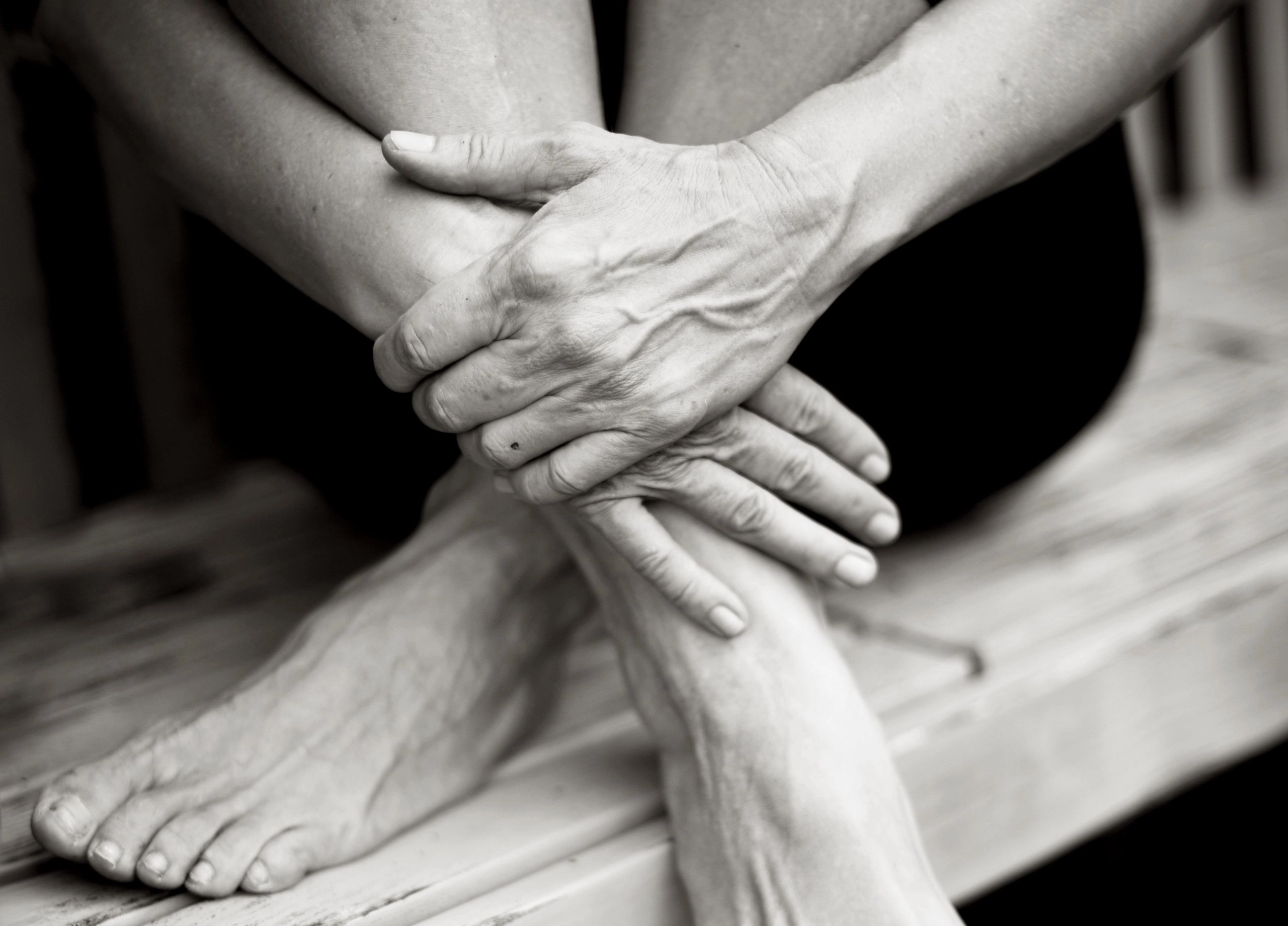 black and white close up of feet and hands