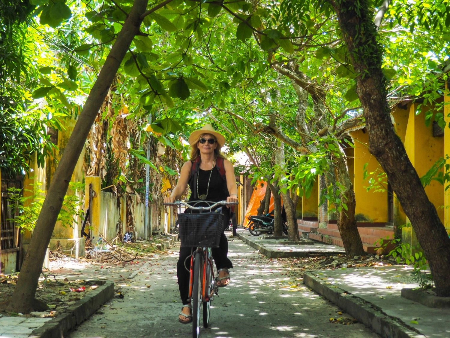 About Kerstin Pilz - Write Your Journey - Always on the lookout for new writing spots. Kerstin Pilz cycling through an alleyway in Hoi An, Vietnam.