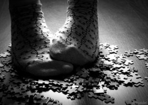 Two feet with puzzle piece socks, standing in a pile of puzzle pieces