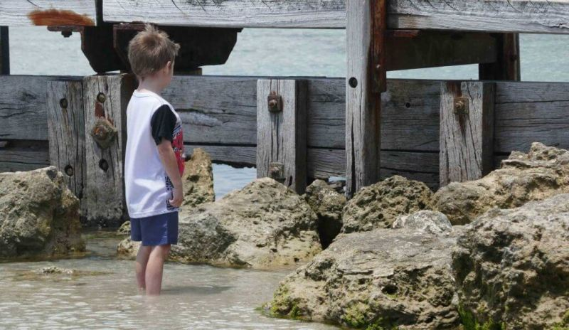 how to build self-esteem in kids child boy at beach staring at bridge