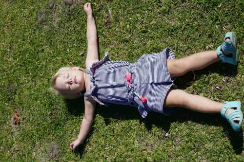 how to build self-esteem in kids toddler girl lying on grass