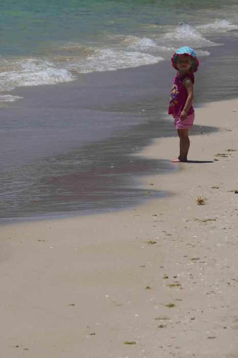 girl toddler standing on the beach