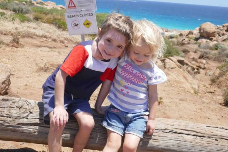 two kids being happy and smiling at the beach