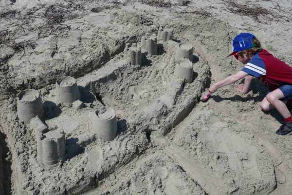 Boy building sandcastles at the beach