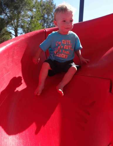 Child toddler going down slide not giving up