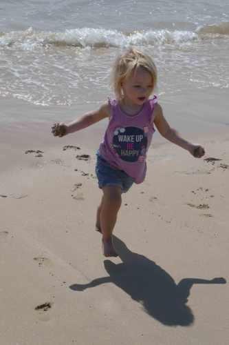 girl running at beach feeling free