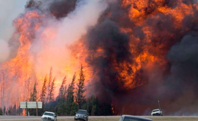 A giant fireball is seen as a wildfire rips through the forest 16 kilometres south of Fort McMurray, Alta. on Highway 63 Saturday, May 7, 2016. THE CANADIAN PRESS/Jonathan Hayward