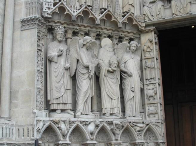 Figury przy wejściu do katedry, w tym św. Dionizy trzymający swoją głowę w rękach