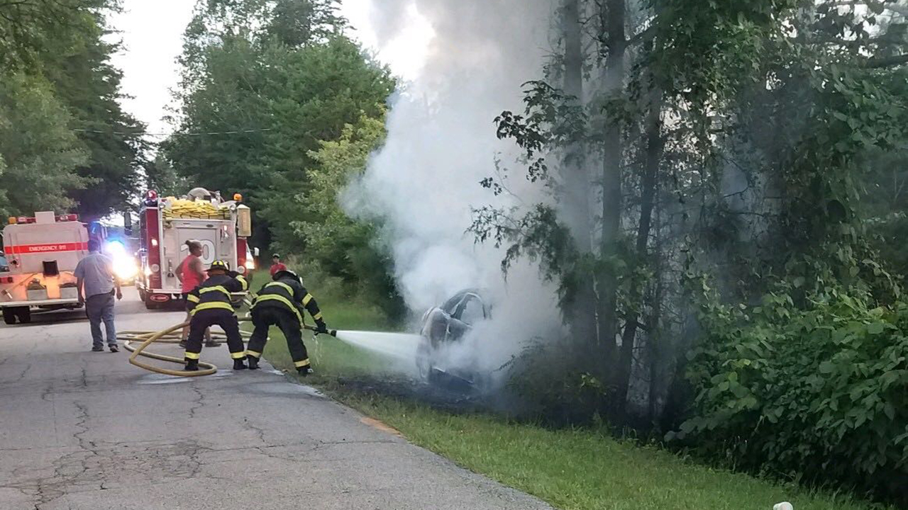 Firefighters work to put out a car fire after a crash along Wilson Creek Road near Iva in Anderson County, Wednesday, July 3, 2019