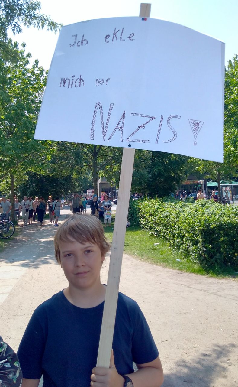 A student protests against the AfD, with sign I am disgusted by nazis!