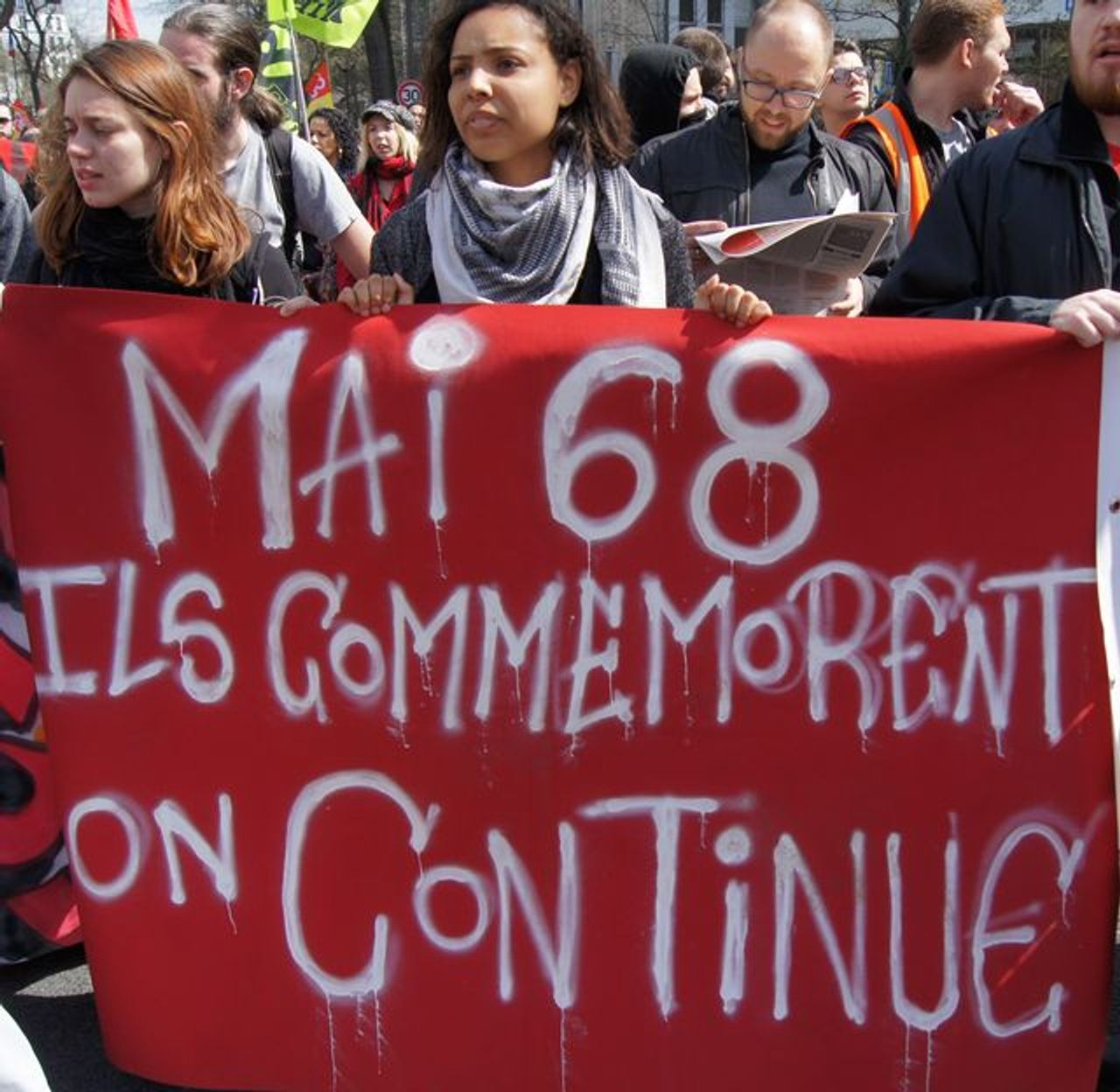 A banner recalls the big May 1968 protests: 'Others commemorate, we continue'