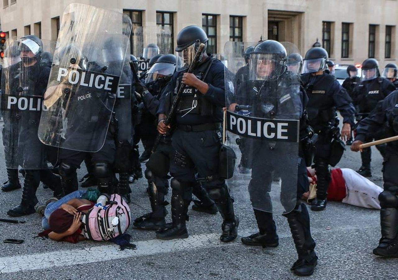 St Louis police in riot geat walk over protesters