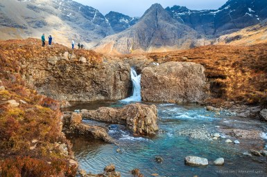 A waterfall at the Fairy Pools, with the Cuillin Mountains in the background. The split in the mountain at the centre of the frame (Sgurr an Fheadain) is known as the Waterpipe Gully.