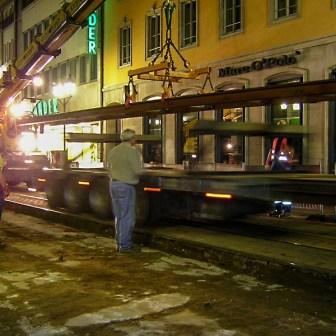 Mit schwerem Gerät werden komplette Schienenstücke verlegt.