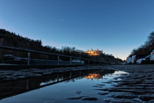 Die Festung Marienberg spiegelt sich in einer Pfütze am Mainufer.