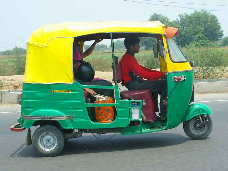 Green and yellow three-wheeled Delhi taxi