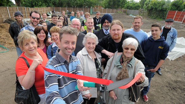 Project coordinator Elliot Lord cuts the ribbon with local residents and volunteers.