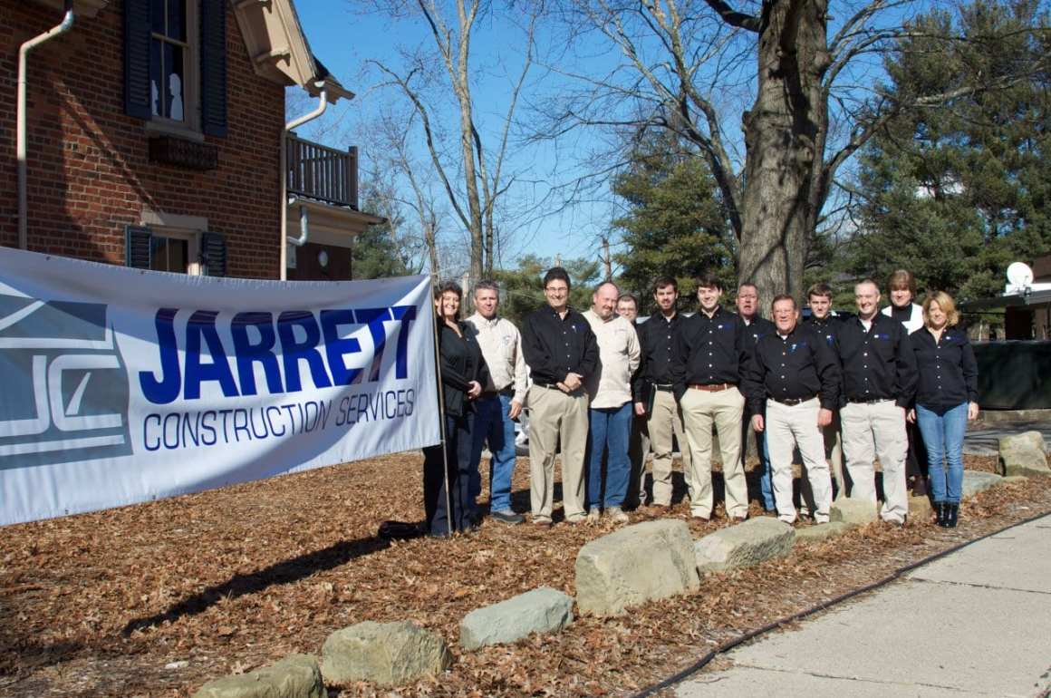 Jarrett Construction Services employees lines up next to a banner with their logo